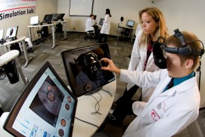 Image 1. A University of Houston College of Optometry student using the Eyesi Indirect simulator (VRmagic, Mannheim, Germany). Pictured are the touchscreen user interface, headband-mounted stereo display, handheld fundus lens and model patient face. Note that the student examiner views the patient images through the stereo display, while the touchscreen user interface simultaneously displays views for the on-looking instructor. Click to enlarge